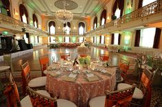The ballroom of the Omni William Penn Hotel in Pittsburgh is lit with orange and green lights, coordinating with the tables, which each feature a solid-color table cloth in green or orange under a sheer white lace topper, satin bows to accent the cane-back chairs, and tan napkins. A three layer wedding cake sits in the center of the room, where guests would later dance to the sounds of The Dreamscape Band. http://www.dreamscapeband.com/weddings.html