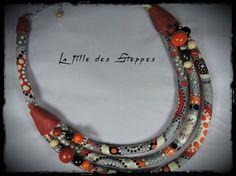 collier LA FILLE DES STEPPES - tissu multicolore à fond gris, cuir rouge et perles métalliques et bois orange, rouges,