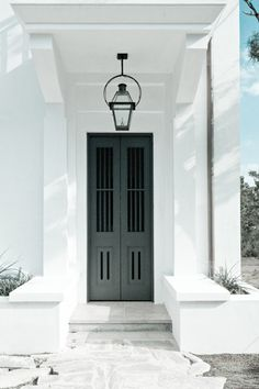 Simplistic and chic entryway. charcoal doors with stone stoop