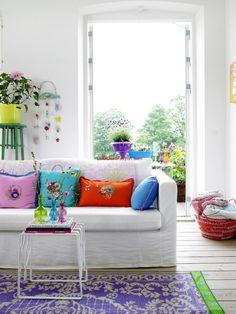 des coussins bariolés et un tapis lilas à motifs blancs