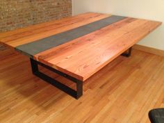 reclaimed wood dinning table with concrete channel down the middle. Its sits on 1/2 plate steel frame. by naan industries