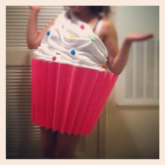 Make the cupcake wrapper from poster paper stuck on a laundry basket that has its bottom cut out. Hold it up with suspenders. Use fleece as the icing and hot glue randomly to scrunch it up. Stick pom pom balls on the fleece as the sprinkles.