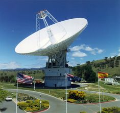 View of Canberra 70m (230 ft.) antenna with flags from the three Deep Space Network sites. The Canberra Deep Space Communications Complex, located outside Canberra, Australia, is one of the three complexes which comprise NASA's Deep Space Network. The other complexes are located in Goldstone, California, and Madrid, Spain. (Great Images in NASA)
