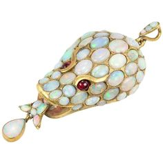 Opal Snake Head Pendant Circa 1870, A unique and whimsical Victorian snake head pendant! The snake head is covered in opals with ruby cabochon eyes in 15 karat yellow gold, circa 1870.