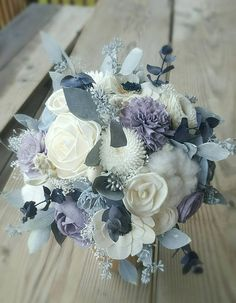 A unique Blend of Everlasting Floral! I use Dusty Lavender and Dusty Slate Blue Sola Flowers and dried Fillers in Cotton, light Grey/powder Blue Seeded Eucalyptus, lambs ear, Baby's Breath and Navy Eucalyptus. I add pops of Anemones with Navy Centers. I can customize the flower types and colors and Fillers! ``Pictured is size Medium bridesmaids and XLarge Bridal``Wedding photos by Shannon Z Photography To purchase coordinating boutonnieres and corsages: https:/&#...