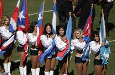 Oakland Raiders cheerleaders hold flags for Hispanic Heritage Month before an NFL football game between the Raiders and the Arizona Cardinals in Oakland, Calif., Sunday, Oct. 19, 2014. (AP Photo/Marcio Jose Sanchez)