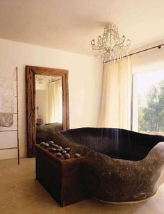 A villa in the remote Santa Agnés valley of Ibiza embodies the owners ambitions to create a 21st-century finca. The magnificent natural granite bath, carved from a single boulder, was shipped from Bali. Above, is a chandelier-cum-overhead shower designed and patented by the owners.    From 'Stone Age', a story on page 190 of Vogue Living Mar/April 2011.    Photograph by Tim Beddow.