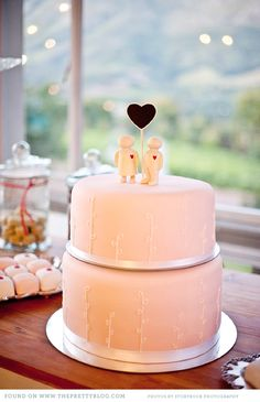 Wedding cake with cake toppers - love the simple white leaf design on the cake!