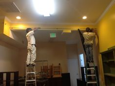 Adding the curtain rod in the back of the store.