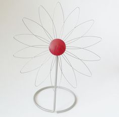 1960s happy little wire daisy with round red metal center, on a sturdy stand, 10 1/4 inches high.   Perfect by itself on a window sill; can hold a small plant in its round base; as a Mad Men desktop photo, business  card, or playing cards display organizer holder.  Unique boudoir jewelry holder.  Retro 60s charm with simplistic design along Scandinavian or industrial lines.  For sale at paroliro on ETSY.  $25.00
