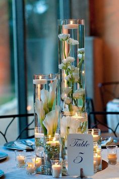 """Other tables will feature a trio of cylinder vases (20"""" tall, 12"""" tall, & 8"""" tall) with submerged white stock flowers, white tulips, and white spray roses with clear crystals in the base and a large floating candle on top, surrounded by skinny cylinders with floating candles and clear fluted votives."""