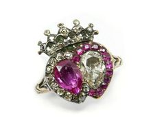 Circa 1780, A ruby and diamond double heart cluster ring, with a pear-shaped ruby surrounded by diamonds, next to a pear-shaped diamond surrounded by rubies. A crown of diamonds sits above, and the stones are set in silver and gold — silver to complement the diamonds, gold to complement the rubies. Again, rings like this often symbolized love (the conjoining of two hearts), while the crown represented loyalty.