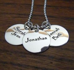 "Mountain Girl Silver.  Necklace with 3 discs.  Kids' names with birthdates.  No pictures.  Papyrus font.  16"" chain.  : )"