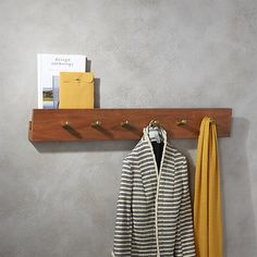Shop hidden channel wall-mounted coat rack.   This is the elegant, everyday, entryway solution you've been waiting for.  Handcrafted of solid, sustainable acacia wood, rack hides a secret top channel to discretely store mail and magazines.
