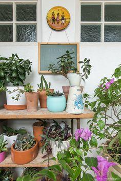 Área de serviço tem pequena estante de madeira para abrigar os vasos e plantas da moradora.
