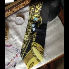Vintage Saxophone Tie Musical Instrument Jazz Band Good condition. In side the part that doesn't show is a little faded. 100% silk the brand is ARTY's. Probably came out in the 1980s. Really fun graphic print symphony lovers. Music. Concert. Scott band. Performer. Jazzy. Festival. Men or women, man, boyfriend gift. Funky. Kistch. Collectible. Dancer. Cosplay. Yellow blue and black. Classic. Vintage Accessories