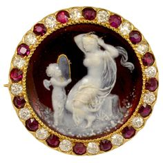 """An intricately detailed turn of the century Tiffany & Co. Venus and Cupid Cameo. The cameo is made with red and white enameling, set on 18k yellow gold, surrounded by Old European cut diamonds and rubies.  Signed on the back """"Venus & Cupid"""" """"Tiffany & Co""""   Circa 1890-1910"""