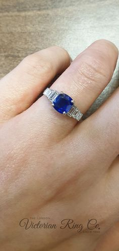This Art Deco style sapphire engagement ring is made to the same design as the original 1930s ring. The carefully selected oval/cushion blue sapphire is held with four claws and highlighted on each side by three baguette cut diamonds. #LondonVictorianRing #BlueSapphires #SapphireRing #SapphireEngagementRing #BaguetteDiamonds #BlueGemstones Blue Sapphire Rings, Blue Gemstones, Baguette Diamond, Designer Engagement Rings, Art Deco Fashion, Claws, Ring Designs, 1930s, Diamond Cuts