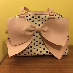 White purse with black polka dots and pink bow Super adorable white bag with black polka dots. Pink bow and straps. There is a small gray spot on the bag but it's not really noticeable. Be prepared to receive tons of compliments. Only used a couple of times. Interested? Make an offer!! ✨ No trades. Betsey Johnson Bags Shoulder Bags