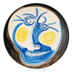 Visage (Face), 1960 Pablo Picasso Madoura round dish of white earthenware clay with decoration in engobes (yellow, blue, black) under glaze