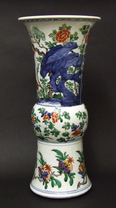 A Transitional Porcelain Vase, Shunzhi Period 1644-1661. This Wucai Gu-Shaped Vase is Decorated with Plants Pomegranate and Scholars Rocks. The Cracked Ice Border Below the Rim in Under-Glaze Cobalt Blue.