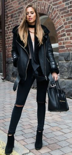 Shearling + all black trend + Kenza Zouiten + stylish winter look + distressed black jeans + leather and shearling jacket + warmth and style Jacket: Acne Studios, Jeans: Asos, Shoes: Jennie-Ellen, Blouse: H&M, Bag: Céline.