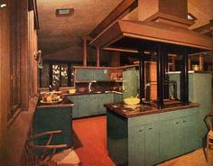 Featured in the February 1957 issue, this easily maintained kitchen has enameled steel cabinets with stainless steel counters, which blend beautifully with the warm quality of wood and plaster surfaces throughout the house. The custom-designed smoke hood over the cooking-top and barbecue is appropriately architectural.