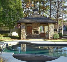 Cool little poolhouse design with a Mediterranean style. Stone walls and covered seating. In ground pool with concrete patio. Fireplace. Wood furniture and doors.