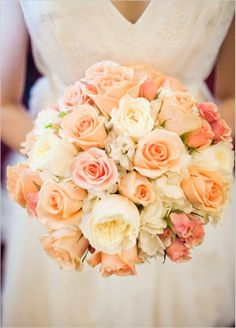 A wedding bouquet with peach and cream roses.