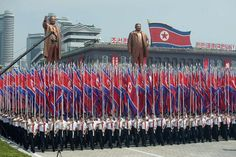 North Koreans wave flags in the country's largest ever military parade