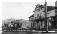 """View of Moffat Avenue, Yampa (Egeria) Routt County, Colorado; signs read: """"The Antlers,"""" """"Saloons,"""" """"Drugs,"""" """"Yampa Restaurant,"""" """"Famous Restaurant & Bakery,"""" and the """"Moffat Avenue Restaurant."""""""