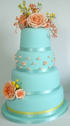Blue cake with orange roses and freesias, and mimosas