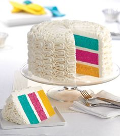 Create this colorful three layer cake- perfect for birthdays or any party! // Zig Zags Over The Rainbow Cake // Find the Wilton how-to on Joann.com