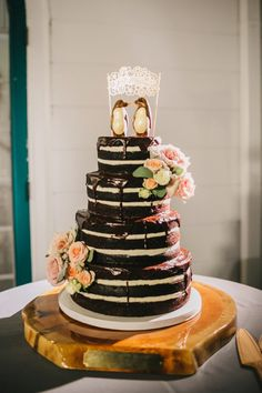 Delicious chocolate naked wedding cake with bird wedding topper | Renee Nicole Photography