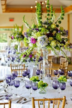 Love the green centerpiece and purple glasses all on a back drop of white!  And a centerpiece that is tall enough that everyone at the table can talk and see one another!!
