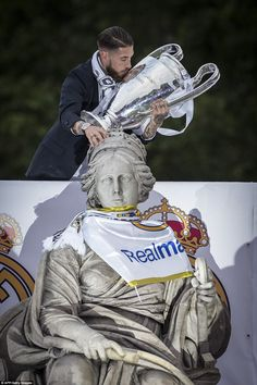 Sergio Ramos, the Real captain, kisses the trophy as he touches the Cybele fountain with a Madrid flag draped around its neck