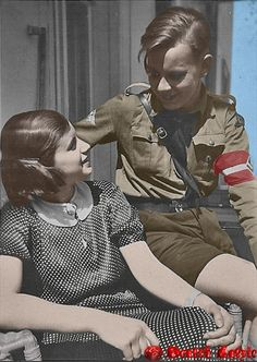 Ein Hitler-Jugend Junge grüßt ein Mädchen und zeigt stolz seine Uniform. A Hitler Youth boy greets a girl and proudly displays his uniform.