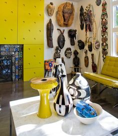 African Influence...  When emulating an African vibe in any room your base color should always be brown. However, if you wish to add a contemporary twist to your interior then incorporate one slice of vibrant color. In the image above you can see how a splash of bright yellow really brings the rest of the room alive – it brings out the intricate carvings of the African wall masks fantastically.  A luscious big green plant can add color and liveliness in a more tamed manner...