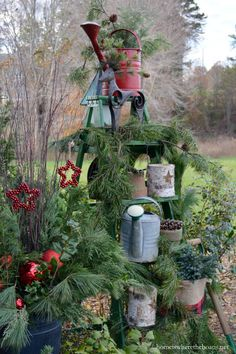 Ladder with watering cans, pine garland, reindeer and lanterns decorated for Christmas | homeiswheretheboatis.net #Christmas #pottingshed