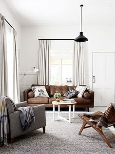 Masculine living space with black pendant chandelier, brown sofa, and small coffee table: