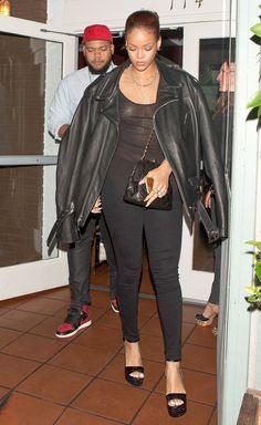 Rihanna wears a sheer black tank top, leather jacket, skinny black pants, and platform sandals