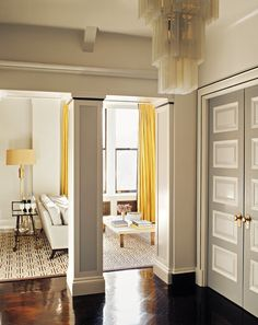 In this prewar Greenwich Village apartment, Steven Gambrel went for a sophisticated European look. He achieved this through stark contrasts. The apartment entry shows this off beautifully — warm yellow curtains stand out against white, black and gray surfaces, and the lacquered wood floor is amplified by the matte paint on the walls and doors.