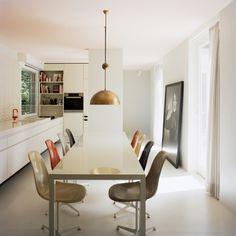 Atrium House by Bfs Design in Tiergarten Park, Berlin, brass pendant in kitchen, multi-colored Eames chairs | Remodelista