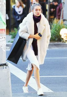 Gigi Hadid wears a white dress with a burgundy scarf, shearling coat, and white sneakers.