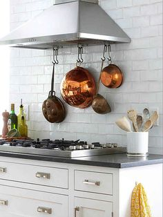 Hang S hooks from a ventilation hood to display pots and pans.