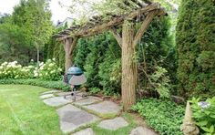"""cedar privacy screen with arbour.  Angled hydrangea """"hedge"""" softens the look"""
