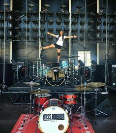 Humor gives Difference to this MOST #POPULAR RE-PIN, dancing on top of a DW Drums Kit on stage. Looks like a festival setup for two band drumkits incl the Miss America Band. #DianaDee #Osborne> I'm filled with #Laughs trying to figure out that REFLECTION in the back #kickdrum! Enlarge the photo to check it out- standing wrong way for photographer! Looks painful standing on that hurt knee...