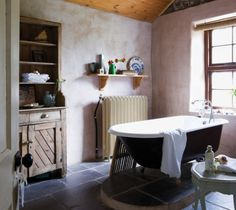 Rustic bathroom with clawfoot tub and large window. Irish Cottage Decor, Cozy Cottage, Cottage Bath, Better Homes And Gardens, Beautiful Bathrooms, Bathroom Interior, Architecture Design, Restored Farmhouse, French Farmhouse