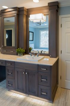 Both sink mirrors are flanked by shelves of storage hidden behind tall, slender doors that are configured in the vanity to mimic columns.  The central section of the vanity has a make-up drawer and more storage behind the mirror.  The base of the cabinetry is filled with a wall of cabinetry and drawers.