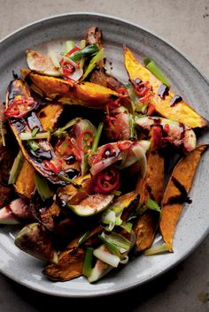 Roasted sweet potatoes, along with wedges of fresh figs, are piled onto a plate